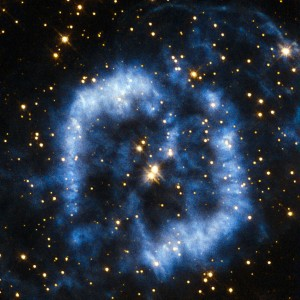 This planetary nebula is called PK 329-02.2 and is located in the constellation of Norma in the southern sky. It is also sometimes referred to as Menzel 2, or Mz 2, named after the astronomer Donald Menzel who discovered the nebula in 1922. When stars that are around the mass of the Sun reach their final stages of life, they shed their outer layers into space, which appear as glowing clouds of gas called planetary nebulae. The ejection of mass in stellar burnout is irregular and not symmetrical, so that planetary nebulae can have very complex shapes. In the case of Menzel 2 the nebula forms a winding blue cloud that perfectly aligns with two stars at its centre. In 1999 astronomers discovered that the star at the upper right is in fact the central star of the nebula, and the star to the lower left is probably a true physical companion of the central star. For tens of thousands of years the stellar core will be cocooned in spectacular clouds of gas and then, over a period of a few thousand years, the gas will fade away into the depths of the Universe. The curving structure of Menzel 2 resembles a last goodbye before the star reaches its final stage of retirement as a white dwarf. A version of this image was entered into the Hubble's Hidden Treasures image processing competition by contestant Serge Meunier.