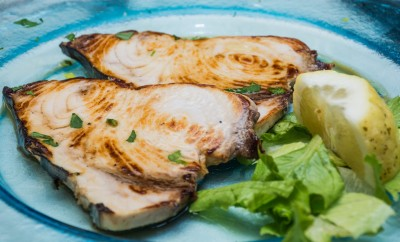 A swordfish dishes pics, among lemons cut, on a glass dish, over a bed of lettuce, ready to eat, in a table spread.